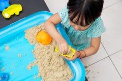 在家演奏运动沙子的亚裔中国小女孩 库存照片