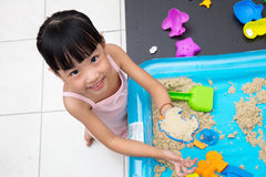 在家演奏运动沙子的愉快的亚裔中国小女孩 图库摄影
