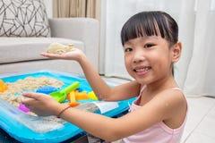 在家演奏运动沙子的愉快的亚裔中国小女孩 免版税库存照片