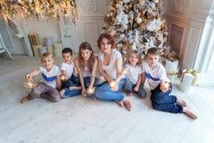 在家演奏闪烁发光物的母亲和五个孩子在圣诞树附近 免版税库存照片