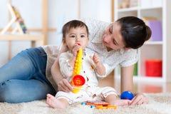 在家演奏音乐玩具的妈妈和婴孩 免版税库存图片