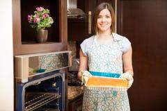 在家烘烤蛋糕的逗人喜爱的妇女 免版税库存图片