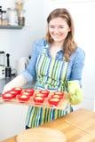 在家烘烤鲜美松饼的俏丽的年轻女人 免版税库存照片