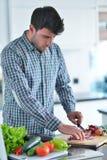 在家烹调准备的英俊的人沙拉在厨房里 免版税库存图片