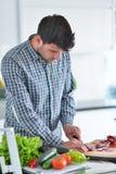 在家烹调准备的英俊的人沙拉在厨房里 免版税库存照片