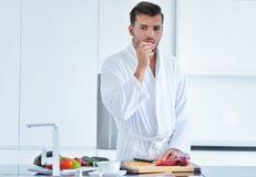 在家烹调准备的英俊的人沙拉在厨房里 库存图片