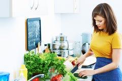 在家烹调厨房的微笑的妇女 免版税库存照片