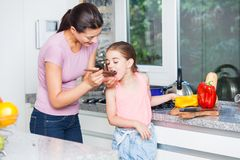 在家烹调厨房的母亲和女儿 免版税库存照片
