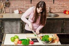 在家烹调在厨房里的少妇 女孩切一个黄瓜并且看片剂 免版税图库摄影