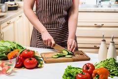 在家烹调在厨房里的少妇 妇女切开一个黄瓜和菜与刀子 库存图片