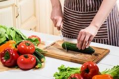 在家烹调在厨房里的少妇 妇女切开一个黄瓜和菜与刀子 图库摄影