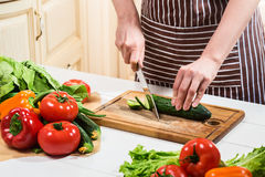 在家烹调在厨房里的少妇 妇女切开一个黄瓜和菜与刀子 免版税库存照片