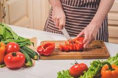 在家烹调在厨房里的少妇 妇女切开胡椒和菜与刀子 库存照片
