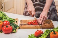 在家烹调在厨房里的少妇 妇女切开胡椒和菜与刀子 免版税库存图片