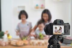 在家烹调在厨房里的母亲和女儿,当录音做录影博客作者照相机 免版税库存图片