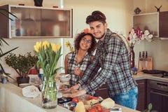 在家烹调在厨房里的美好的年轻夫妇 免版税图库摄影