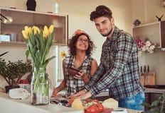 在家烹调在厨房里的美好的年轻夫妇 免版税库存图片