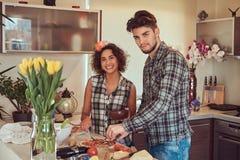 在家烹调在厨房里的美好的年轻夫妇 库存照片