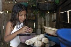 在家烹调在厨房里的玻利维亚的女孩 免版税图库摄影