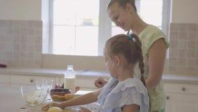 在家烹调蛋糕的年轻女人和她的小女儿侧视图在厨房里 女孩完成的工作和上流 股票录像