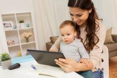 在家照顾有婴孩和片剂个人计算机的学生 免版税库存照片