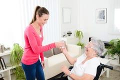 在家照顾轮椅的一名年长妇女的快乐的少妇 免版税库存图片