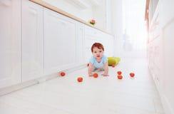 在家爬行在地板上的逗人喜爱的姜男婴 免版税图库摄影