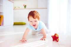 在家爬行在地板上的逗人喜爱的姜男婴 免版税库存图片