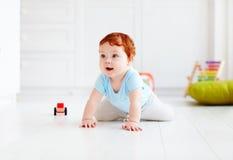 在家爬行在地板上的逗人喜爱的婴儿婴孩 免版税库存照片