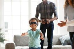 在家玩捉迷藏的愉快的非洲家庭 免版税图库摄影