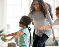 在家玩捉迷藏的愉快的非裔美国人的家庭 免版税图库摄影