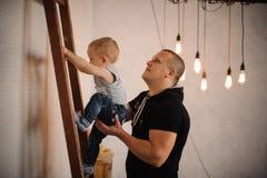 在家生帮助他的慢慢地上升小伙子的小儿子 库存图片