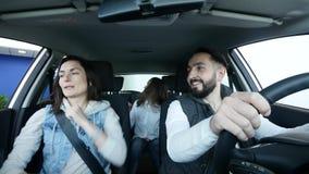 在家用汽车的愉快的微笑的家庭跳舞 图库摄影
