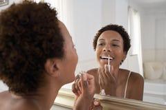 在家申请在镜子的妇女嘴唇光泽 免版税库存图片