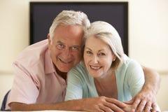 在家看宽银幕电视的资深夫妇 图库摄影