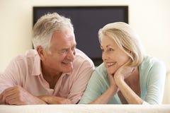 在家看宽银幕电视的资深夫妇 免版税图库摄影