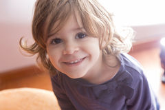在家看照相机的可爱的小女孩 免版税库存图片