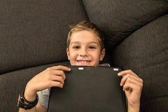 在家看片剂的沙发的孩子 库存图片
