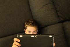 在家看片剂的沙发的孩子 免版税库存图片