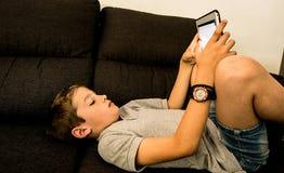 在家看片剂的沙发的孩子 库存照片