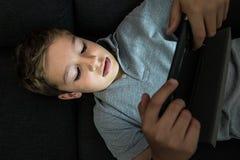 在家看片剂的沙发的孩子 图库摄影