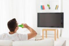 在家看电视和喝啤酒的人 库存照片