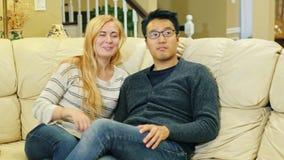 在家看电视的不同种族的夫妇 亚裔男人和白种人妇女 坐长沙发,保持遥控手中 股票视频