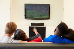 在家看电视的两对年轻夫妇一起 库存照片
