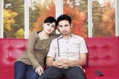 在家看电视的哀伤的夫妇 免版税库存照片