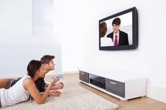 在家看电视的夫妇 免版税图库摄影