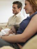在家看电视的女孩和父母 免版税库存图片