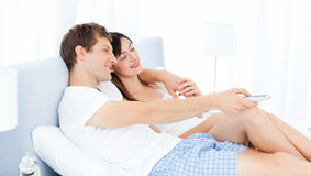 在家看电视的微笑的夫妇 免版税图库摄影