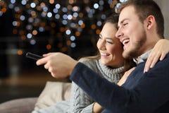 在家看电视的滑稽的夫妇在冬天 库存图片