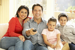 在家看电视的年轻西班牙家庭 免版税库存照片